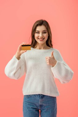 Smiling brunette girl holding credit card and showing thumb up isolated on pink stock vector