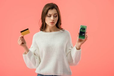 Attractive brunette girl holding credit card while looking at smartphone with booking app on screen isolated on pink stock vector