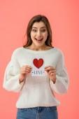 šťastná mladá žena držící kartu s nápisem love izolované na růžové