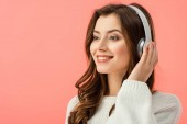 Fotografie smiling and beautiful woman in white sweater listening music with headphones isolated on pink