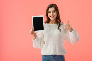 Happy young woman holding digital tablet with blank screen and showing thumb up isolated on pink stock vector