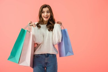 smiling and attractive woman in white sweater holding shopping bags isolated on pink