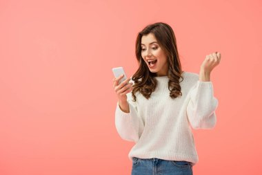 surprised and attractive woman in white sweater holding smartphone isolated on pink
