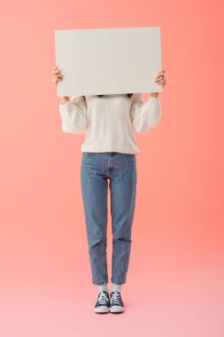 full length view of woman in white sweater and jeans holding empty board with copy space