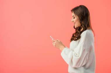 smiling and attractive woman in white sweater holding smartphone isolated on pink
