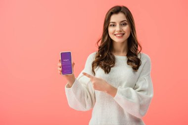 woman in white sweater pointing with finger at smartphone with instagram app on screen isolated on pink
