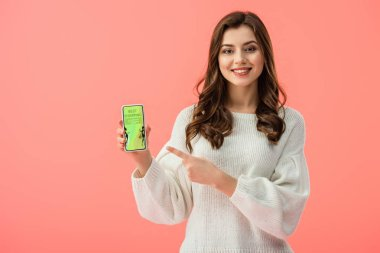 woman in white sweater pointing with finger at smartphone with best shopping app on screen isolated on pink