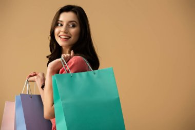 smiling and beautiful woman holding shopping bags isolated on beige