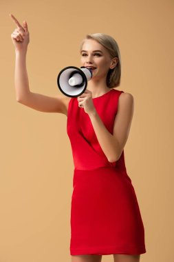 woman in red dress screaming in megaphone and pointing with finger isolated on beige