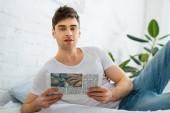 Selektivní fokus pohledný muž ležící na posteli s novinami doma