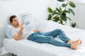 muž v bílé tričko a džíny, ležel na posteli a čtení noviny doma