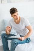 pohledný muž v bílé tričko a džíny sedí na posteli s novinami doma