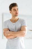 Fotografie schöner Mann in weißem T-Shirt steht mit verschränkten Armen im Schlafzimmer