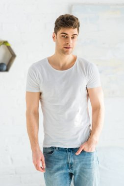 Handsome man in white t-shirt and jeans standing on white background stock vector