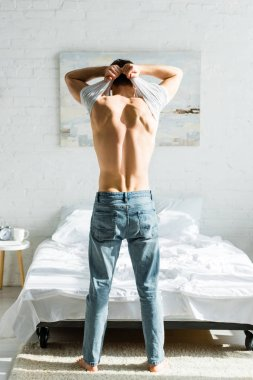man in jeans standing backwards near bed and taking off white t-shirt in bedroom
