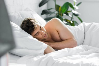 handsome man sleeping on bed with bare torso in bedroom