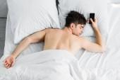 jóképű férfi, üres képernyő, a rossz takaró közelében smartphone alatt alszik