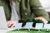 Selektiver Fokus von Sonnenkollektoren und Baummodellen auf dem Tisch in der Nähe des Architekten im Büro