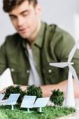 Selektivní fokus architekta u stolu s větrným mlýnem, stromy, modely solárních panelů v úřadu