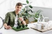 pohledný architekt, usmíval se a drží modely solárních panelů nad trávy na stole v kanceláři