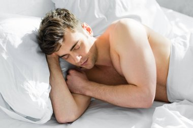 Handsome man sleeping on side with bare torso on bed in bedroom stock vector