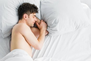 top view of handsome man sleeping on bed under blanket with bare torso at home
