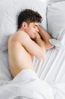 top view of handsome man sleeping under blanket with bare torso at home