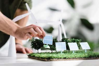 cropped view of man putting solar panels models on grass on table in office