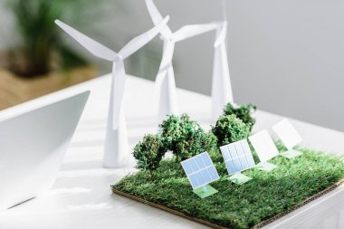 Table with trees, windmills and solar panels models on grass in office stock vector