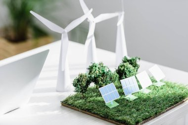 table with trees, windmills and solar panels models on grass in office