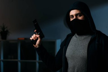 Robber in mask holding gun and looking at camera in dark room