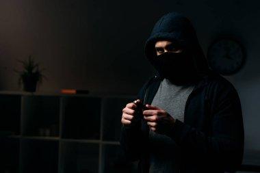 Burglar in mask standing in dark room and holding keys