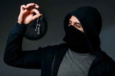Criminal in black mask and hoodie looking at keys