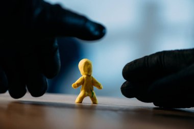 Partial view of thief in black gloves stealing yellow toy