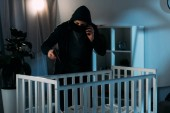 Photo Criminal in mask talking on smartphone and aiming gun in crib