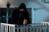 Photo Kidnapper in black mask standing beside crib and looking at camera