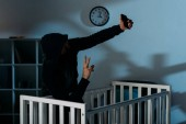 Fotografie Kidnapper taking selfie near crib and showing peace sign