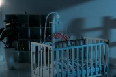Photo Cupboard, crib and mobile with toys in dark nursery