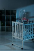 Photo Crib with mobile and cupboard standing in dark room