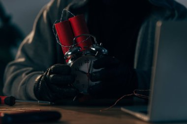 Partial view of criminal in leather gloves holding bomb