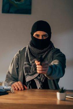 Criminal in black mask and scarf aiming gun at camera stock vector