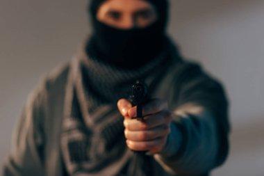 Terrorist in mask and scarf aiming gun at camera