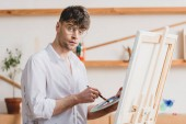 handsome artist in glasses standing at easel with palette and paintbrush and looking at camera