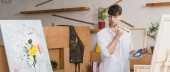 panoramic shot of handsome artist with paintbrush and palette looking at painting in painting studio