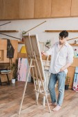 handsome artist in white shirt and blue jeans painting on canvas