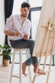 handsome artist in white shirt and blue jeans mixing paints on palette while sitting at easel in gallery