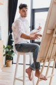 handsome artist in white shirt and blue jeans painting on canvas in gallery
