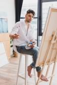 pohledný umělec s paletou a štětcem, sedí na židličku a při pohledu na fotoaparát
