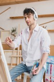 selective focus of handsome artist listening music with headphones