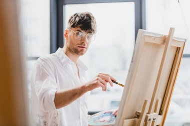 selective focus of handsome artist in glasses looking at camera while drawing on canvas